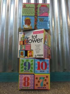 """The Tot Tower (ages 2+) provides 10 sturdy blocks to, """"stack, nest, and topple down."""" With charming illustrations and poems on each side, they're sure to inspire hours of creative play!"""